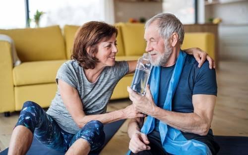 Una pareja bebe agua para mantenerse hidratados