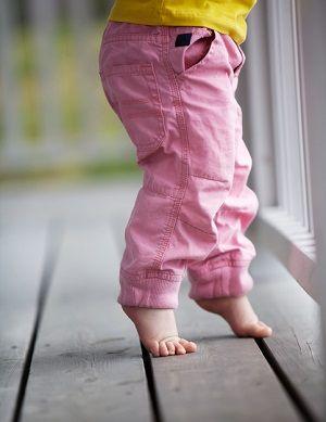 Un bebé, andando de puntillas