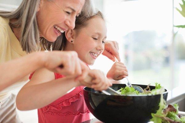 Abuela y nieta preparando una ensalada